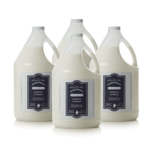 Four bottles of Beekman 1802 Dispensary Conditioner to be used in hotel amenity dispensers.